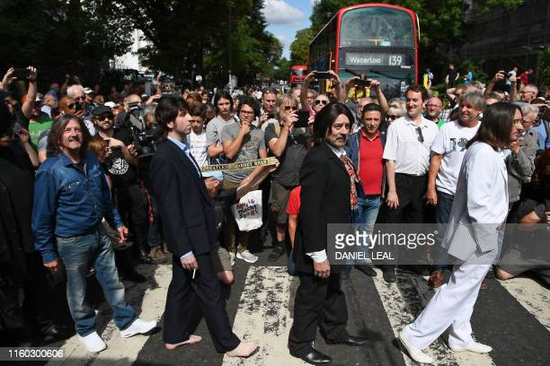 Beatles lookalike band 'Fab Gear' and fans of The Beatles pose at the famous Abbey Road zebra crossing in London England on August 8 the 50th...