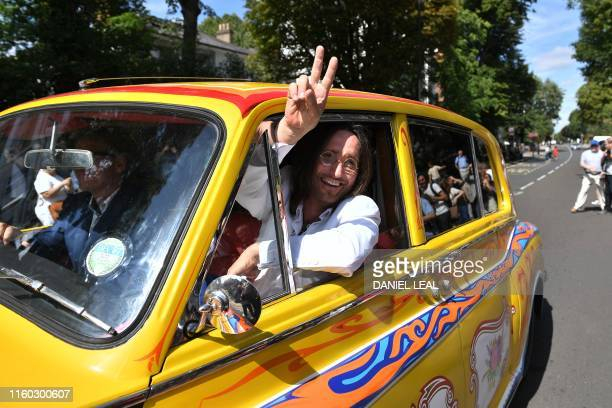 Beatles lookalike band 'Fab Gear' member John Lennon waves from his replica psychedelic rolls royce after joining fans at the famous Abbey Road zebra...