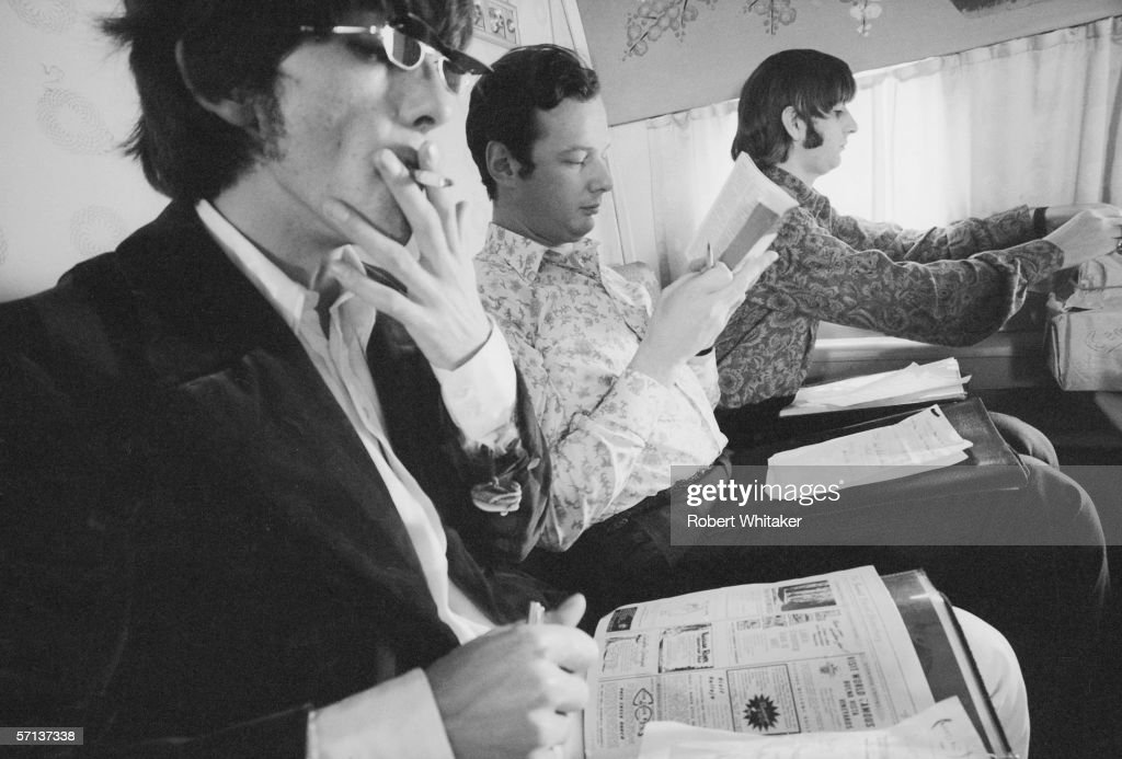 Beatles' manager Brian Epstein (1934 - 1967) sits between George (left) and Ringo en route to Manila in the Philippines, during the band's Asian tour, 4th July 1966.