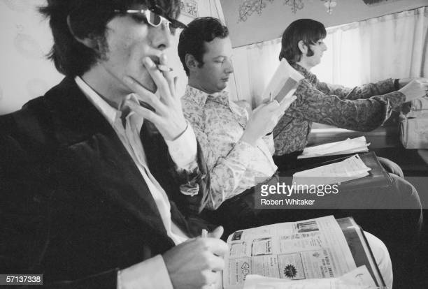 Beatles' manager Brian Epstein sits between George and Ringo en route to Manila in the Philippines during the band's Asian tour 4th July 1966