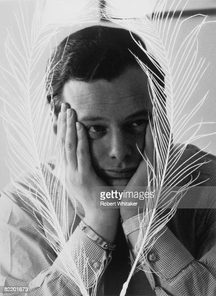 Beatles manager Brian Epstein with his face framed by peacock feathers during a tour of Australia June 1964