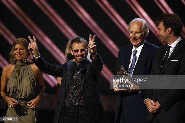 Beatles member Ringo Starr flashes a double victory sign as producer George Martin holds the trophy for Best Compilation Soundtrack Album at the 50th...