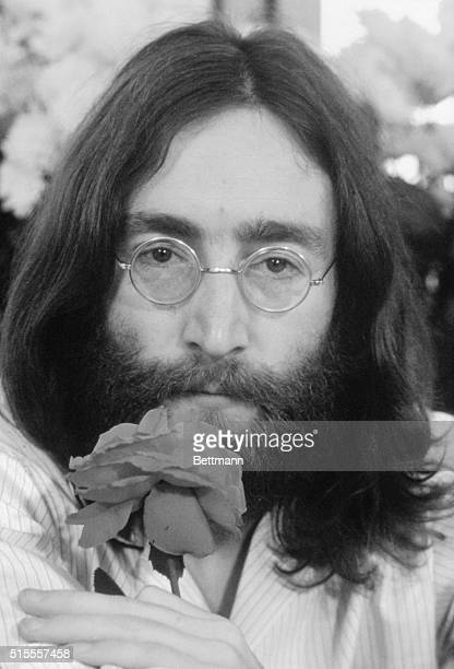Beatles musician John Lennon holding a rose during his 'Bed for Peace' demonstration