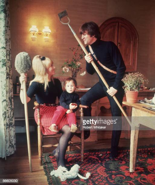 Beatles singer songwriter and guitarist John Lennon at home with his first wife Cynthia and their son Julian 1964 John holds a hoe and Cynthia has a...