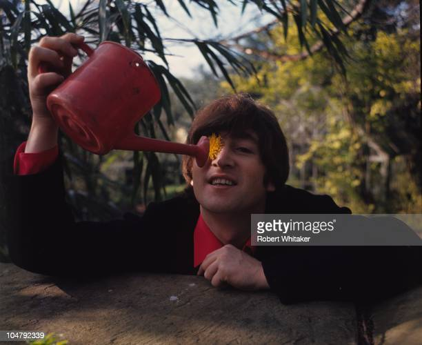 Beatles singer songwriter and guitarist John Lennon in the garden at his home at Kenwood Weybridge Surrey 1964 He is pretending to water a dandelion...