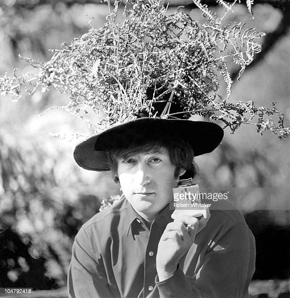 Beatles singer songwriter and guitarist John Lennon in the garden at his home at Kenwood Weybridge Surrey 1964 He is holding a porcelain jar and...