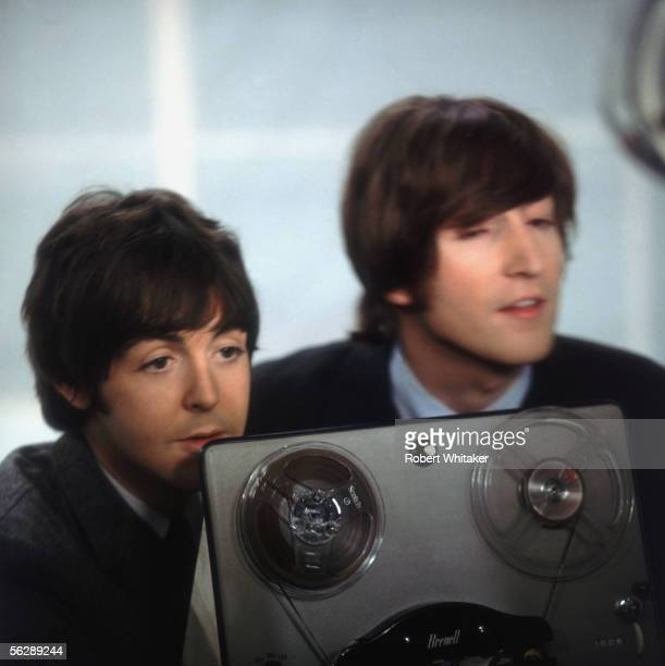 Beatles stars Paul McCartney and John Lennon pictured on set during a break from recording a Granada television programme 1965