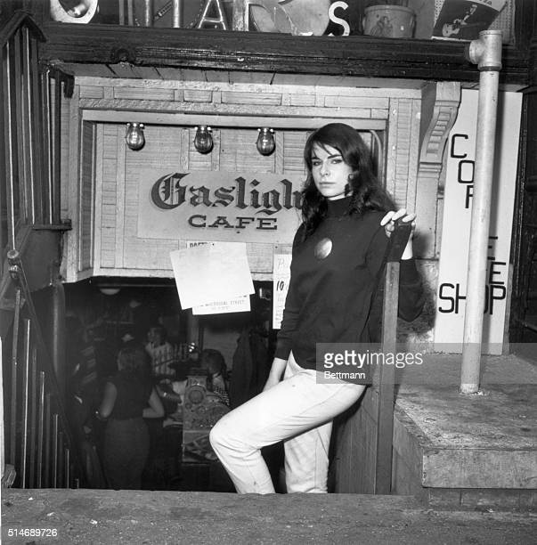 A beatnik woman stands in front of the entrance to the Gaslight Cafe a center of beatnik poet life in Greenwich Village New York