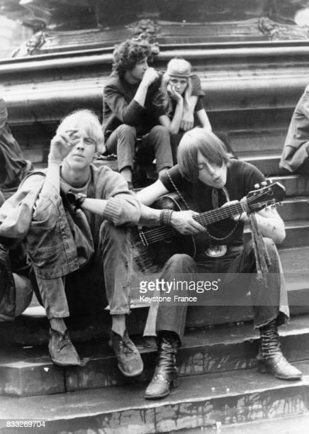 Beatniks assis sur des marches de Picadilly Circus écoutant et jouant de la musique à Londres RoyaumeUni le 19 août 1969