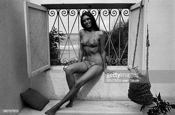 Beatrice Barclay Presents Her New Swimwear Collection 1971 En Tunisie sur la terrasse d'une villa Béatrice CHATELIER assise sur un rebord de fenêtre...