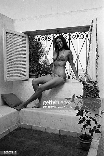 Beatrice Barclay Presents Her New Swimwear Collection 1971 En Tunisie sur la terrasse d'une villa Béatrice CHATELIER assise sur un rebord de fenêtre...