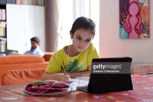 Beatrice Buono participates in distance lessons with her teacher while her father Giuseppe Buono is working from home on May 11 2020 in Milan Italy...