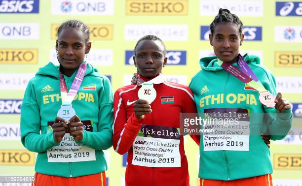 Beatrice Chebet of Kenya Alemitu Tariku and Tsigie Gebreselama of Ethiopia pose for a photograph with their medals following the IAAF World Athletics...
