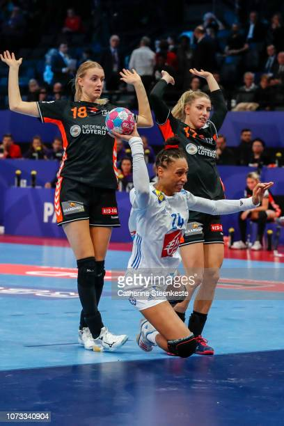 Beatrice Edwige of France is shooting the ball against Kelly Dulfer and Nycke Groot of Netherlands during the EHF Euro semi-final match between...