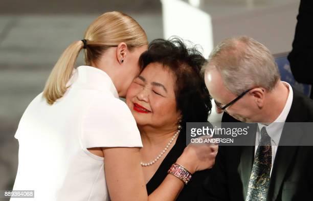 Beatrice Fihn leader of ICAN hugs Hiroshima nuclear bombing survivor Setsuko Thurlow as Henrik Syse member of the Norwegion Nobel Committee looks on...
