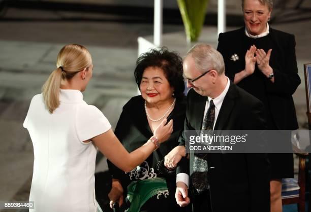 Beatrice Fihn leader of ICAN hugs Hiroshima nuclear bombing survivor Setsuko Thurlow as Henrik Syse member of the Norwegion Nobel Committee and Berit...