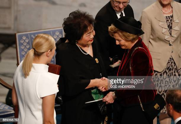 Beatrice Fihn leader of ICAN looks on as Hiroshima nuclear bombing survivor Setsuko Thurlow is congratulated by Queen Sonja of Norway during the...