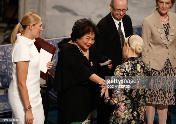 Beatrice Fihn leader of ICAN looks on as Hiroshima nuclear bombing survivor Setsuko Thurlow is congratulated by Crown Princess MetteMarit of Norway...