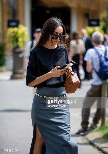 Beatrice Gutu is seen wearing mini Loewe bag silk skirt with slit black top outside Redemption during Paris Fashion Week Haute Couture Fall/Winter...