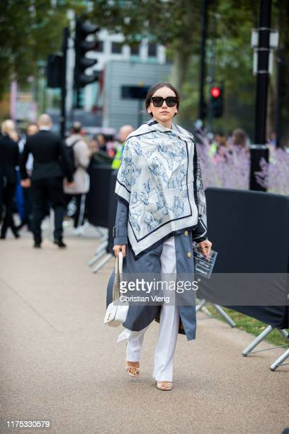 Beatrice Gutu is seen wearing scarf with print, grey coat, white pants, bag outside Burberry during London Fashion Week September 2019 on September...
