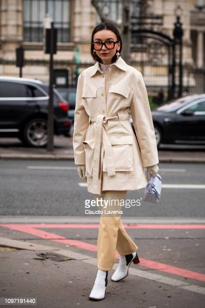 Beatrice Gutu wearing a light beige trench coat beige trousers white boots and lilac Acne bag is seen in the streets of Paris before the Acne Femme...