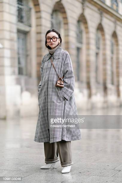 Beatrice Gutu wears a checked gray long coat a wool turtleneck white shoes earrings a brown mini bag outside Alexis Mabille during Paris Fashion Week...