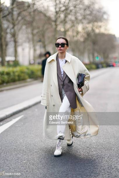 Beatrice Gutu wears sunglasses, a white long coat, a brown jacket, white shoes, a bag, cuffed pants, outside Paul Smith, during Paris Fashion Week -...