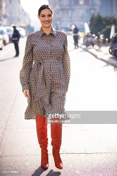 Beatrice Valli, wearing a printed shirt dress and orange boots, is seen outside Salvatore Ferragamo show, during Milan Fashion Week Fall/Winter...