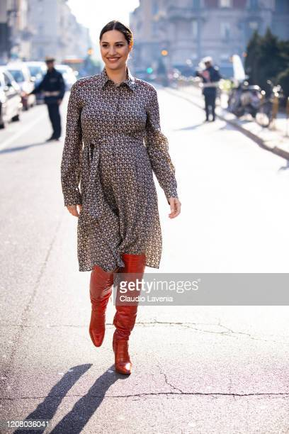 Beatrice Valli, wearing monogram Salvatore Ferragamo dress and red boots, is seen outside Salvatore Ferragamo show, during Milan Fashion Week...
