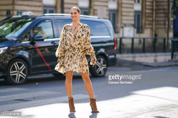 Beatrice Valli wears a Vneck beige and brown spotted gathered and flowing mini dress with long sleeves brown pointy heeled ankleboots outside...