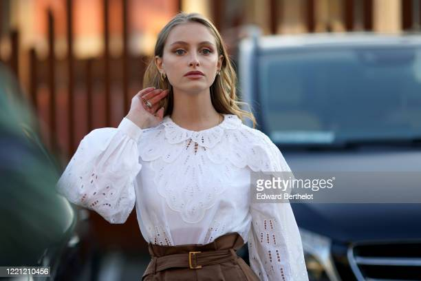 Beatrice Vendramin wears a white ruffled lace top with puff shoulders, earrings, outside Alberta Ferretti, during Milan Fashion Week Fall/Winter...
