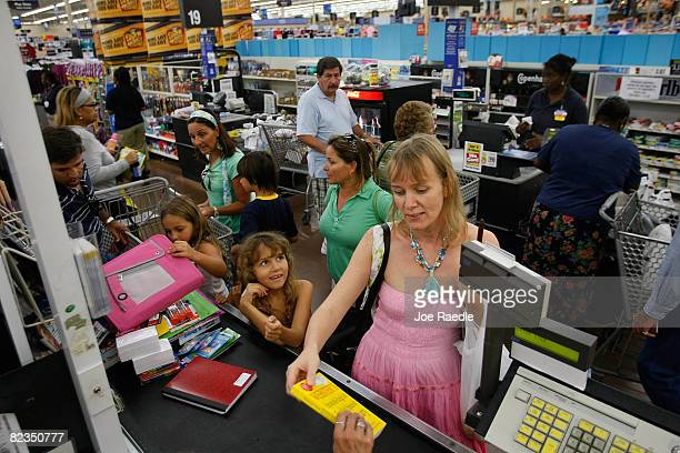 Beatrix Csinger and Samarah Uriarte 8yearsold go through the checkout as they make purchases at a WalMart Store August 14 2008 in North Miami Florida...
