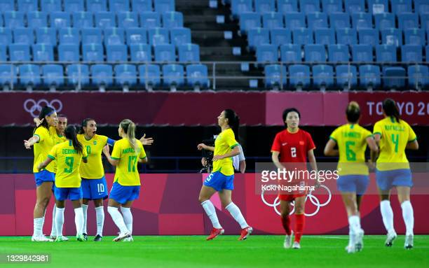 Beatriz of Team Brazil celebrates with Marta and teammates after scoring their side's fifth goal during the Women's First Round Group F match between...
