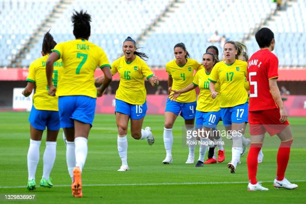 Beatriz of Team Brazil congratulates teammate Debinha after scoring their side's second goal during the Women's First Round Group F match between...