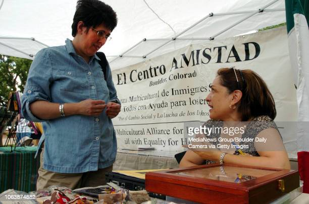 Beatriz Pestana left and Elena Aranda talk about political issues in Venezuela on Saturday in the El Centro Amistad booth at the INTERdependence Day...