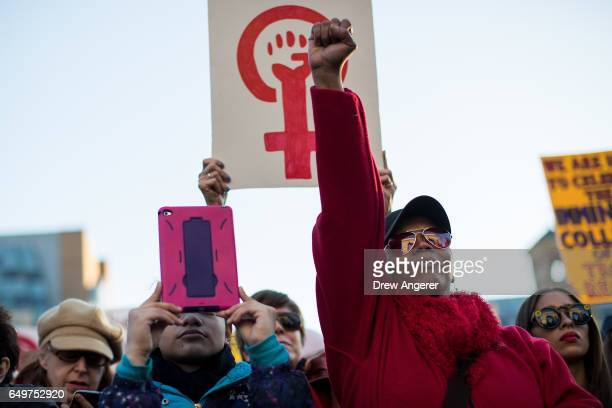 Beatriz Prado from the Bronx holds up her fist as she cheers during a rally to mark International Women's Day in Washington Square Park March 8 2017...