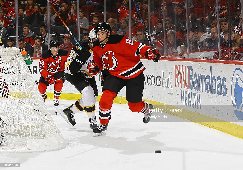 Beau Bennett #8 of the New Jersey Devils and David Pastmak #88 of the Boston Bruins battle for a loose puck during the game at Prudential Center on January 2, 2017 in Newark, New Jersey.