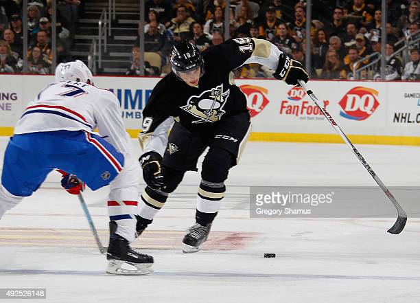Beau Bennett of the Pittsburgh Penguins moves the puck in front of Tom Gilbert of the Montreal Canadiens at Consol Energy Center on October 13 2015...