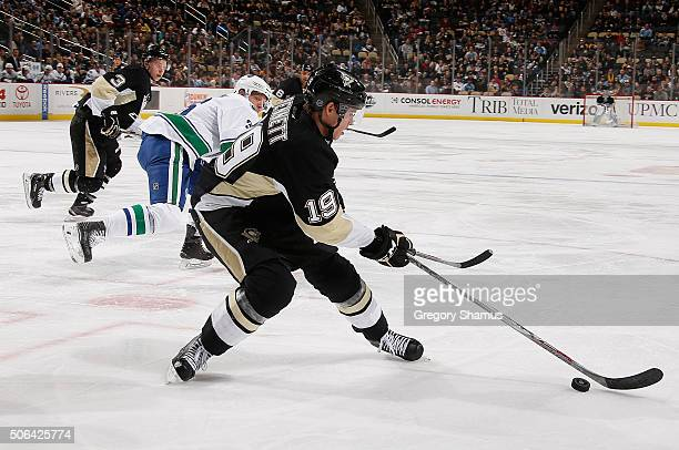 Beau Bennett of the Pittsburgh Penguins moves the puck in front of Jannik Hansen of the Vancouver Canucks during the second period at Consol Energy...