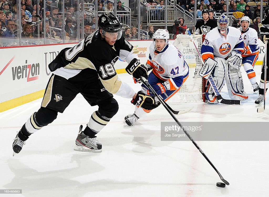 Beau Bennett #19 of the Pittsburgh Penguins reaches for the loose puck in front of Andrew MacDonald #47 of the New York Islanders on March 10, 2013 at Consol Energy Center in Pittsburgh, Pennsylvania.