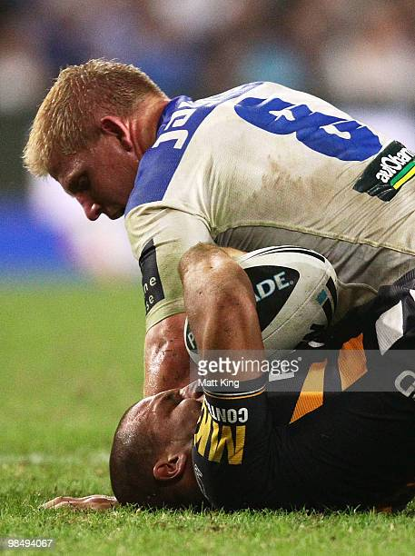 Beau Ryan of the Tigers is tackled by Ben Hannant of the Bulldogs during the round six NRL match between the Wests Tigers and the Canterbury Bulldogs...