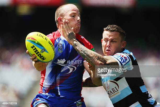 Beau Scott of the Knights gets the ball past Todd Carney of the Sharks during the match between Cronulla Sharks and the Newcastle Knights in the...