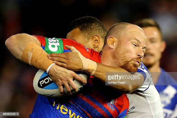 Beau Scott of the Knights is tackled by the Bulldogs defence during the round 25 NRL match between the Newcastle Knights and the Canterbury Bulldogs...