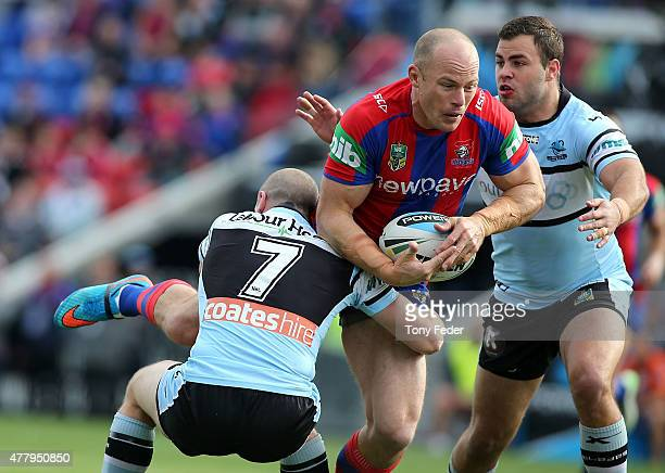 Beau Scott of the Knights is tackled by the Sharks defence during the round 15 NRL match between the Newcastle Knights and the Cronulla Sharks at...