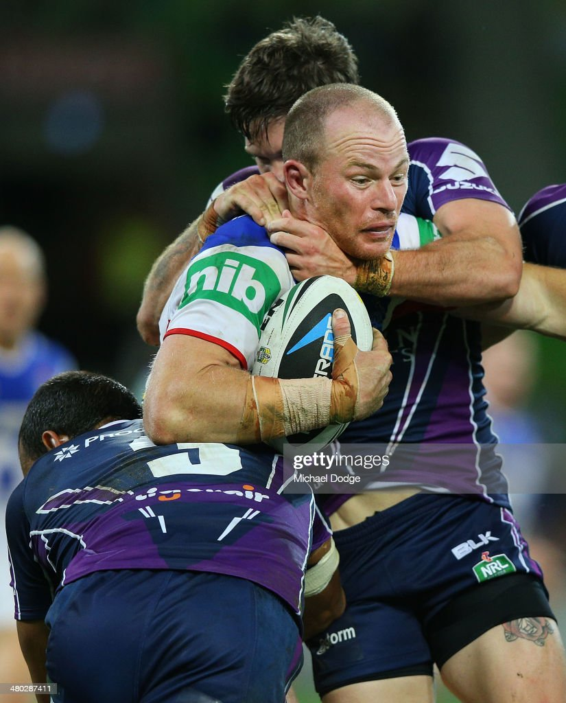 Beau Scott of the Knights is tackled by Will Chambers and Ben Hampton (R) of the Storm during the round three NRL match between the Melbourne Storm and the Newcastle Knights at AAMI Park on March 24, 2014 in Melbourne, Australia.