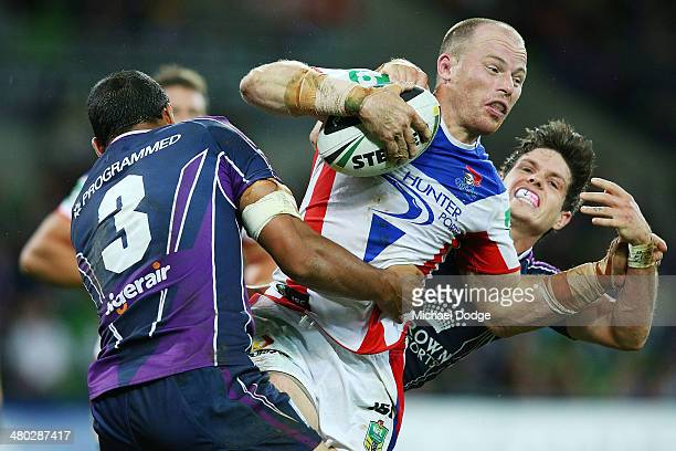 Beau Scott of the Knights is tackled by Will Chambers and Ben Hampton of the Storm during the round three NRL match between the Melbourne Storm and...