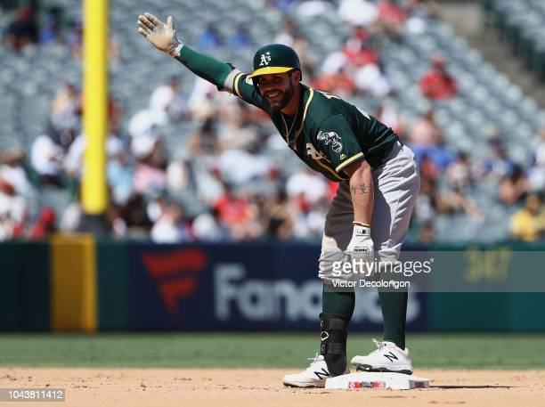 Beau Taylor of the Oakland Athletics gestures to the Athletics dugout after falling to the dirt on his way to second base on a double to deep right...