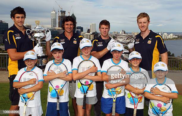 Beau Waters Andrew Embley Josh Kennedy and Ashley Hansen of the West Coast Eagles pose with the Australian Open Trophies and junior tennis players...