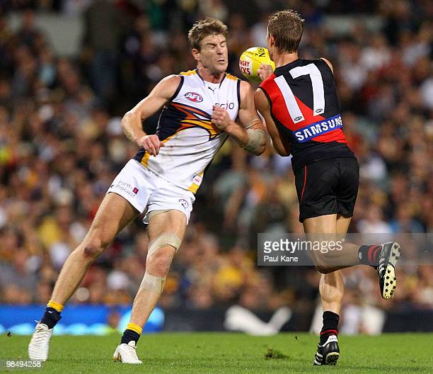Beau Waters of the Eagles bumps Jake Melksham of the Bombers during the round four AFL match between the West Coast Eagles and the Essendon Bombers...
