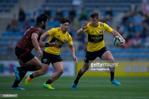 Beauden Barrett of Suntory Sungoliath hands off Yu Chinen od Toshiba Brave Lupus during the Top League match between Toshiba Brave Lupus and Suntory...